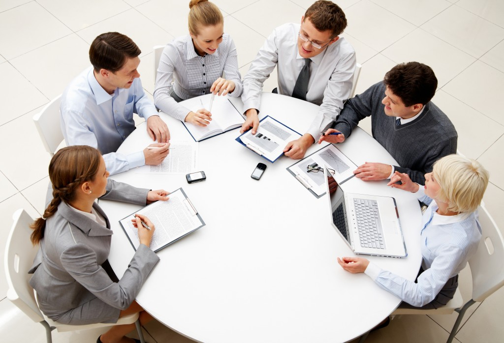 Image of company of successful partners discussing business plan at meeting